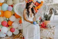 a boho lace white maxi dress with a deep neckline, no sleeves and a bright floral crown for a chic summer boho look