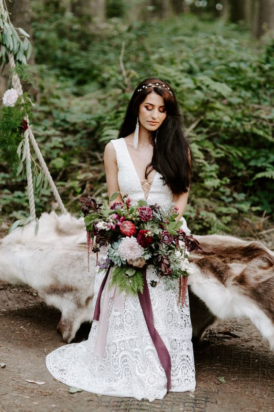 a boho woodland bride wearing a boho lace sleeveless wedding dress with a plunging neckline, a bold bouquet with greenery and tassel earrings