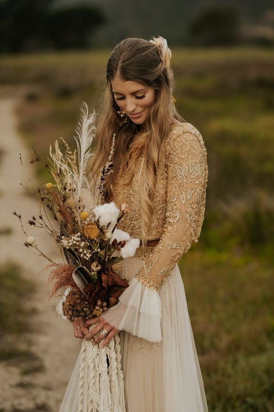 a boho woodland bride wearing an embellished top with bell sleeves, a layered skirt, a boho fall bouquet with dried elements