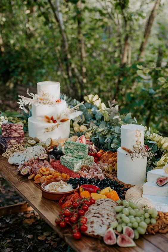 a boho woodland dessert table with greenery, pretty cakes, cheeses, meat and fresh veggies and berries is a great idea