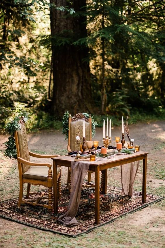 a boho woodland reception table with a taupe runner, candles, feathers and gilded glasses and greenery is very chic