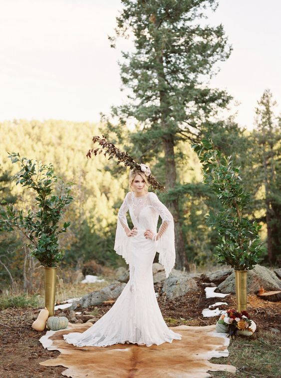 a boho woodland wedding altar with greenery in gold vases, pumpkins, blooms and animal skins