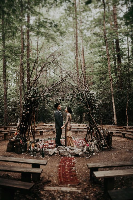 a boho woodland wedding arch of branches, greenery and white blooms, boho rugs and rocks on the ground