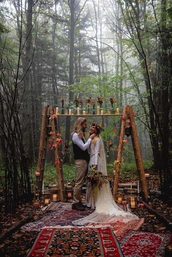 a boho woodland wedding arch of wood, with candles, bold leaves and blooms and boho rugs just wows