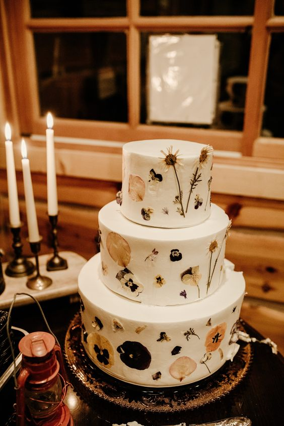 a boho woodland wedding cake with pressed dried blooms and foliage is a perfect idea for a fall boho wedding