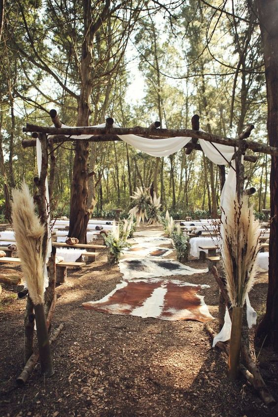 a boho woodland wedding space with a wooden arch with fabric and pampas grass, with animal skins and greenery and pampas grass around