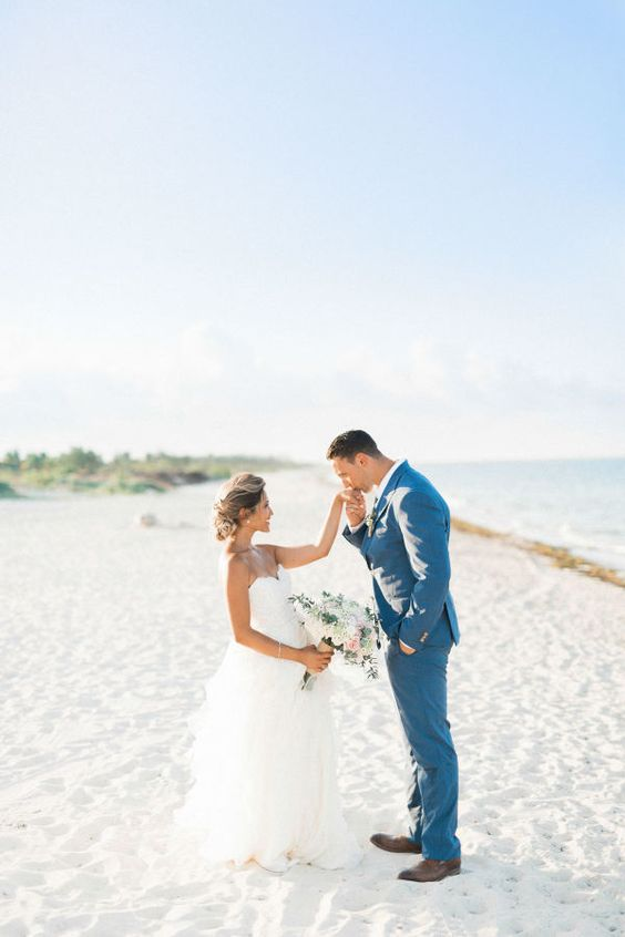 a bold blue groom's suit paired with a white shirt and brown shoes for a blue beach wedding