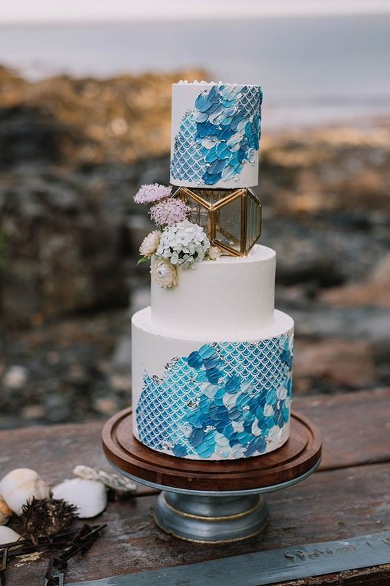 a bold blue wedding cake with a print and brushstrokes, with blooms and a candle lantern in its center