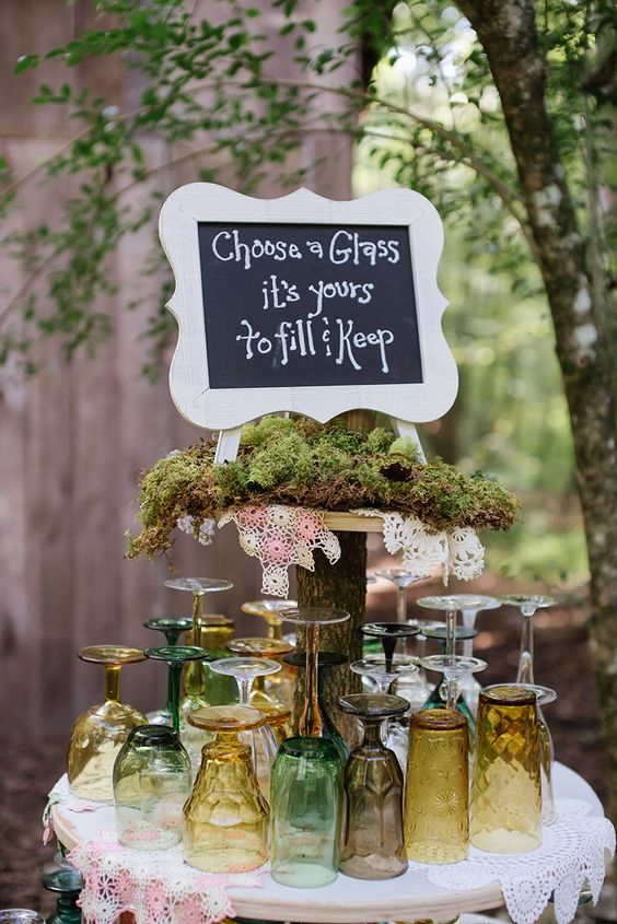a bold woodland wedding station with colorful glasses, moss and doilies and a chalkboard sign in a frame is a chic idea with a boho feel