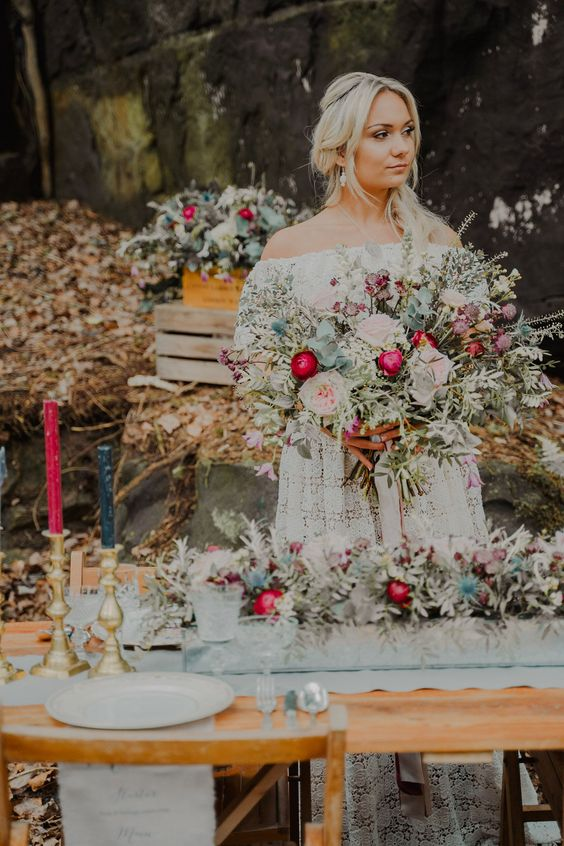 a bright boho wedding tablescape with colorful candles, bold blooms and gold touches, neutral porcelain and lots of greenery