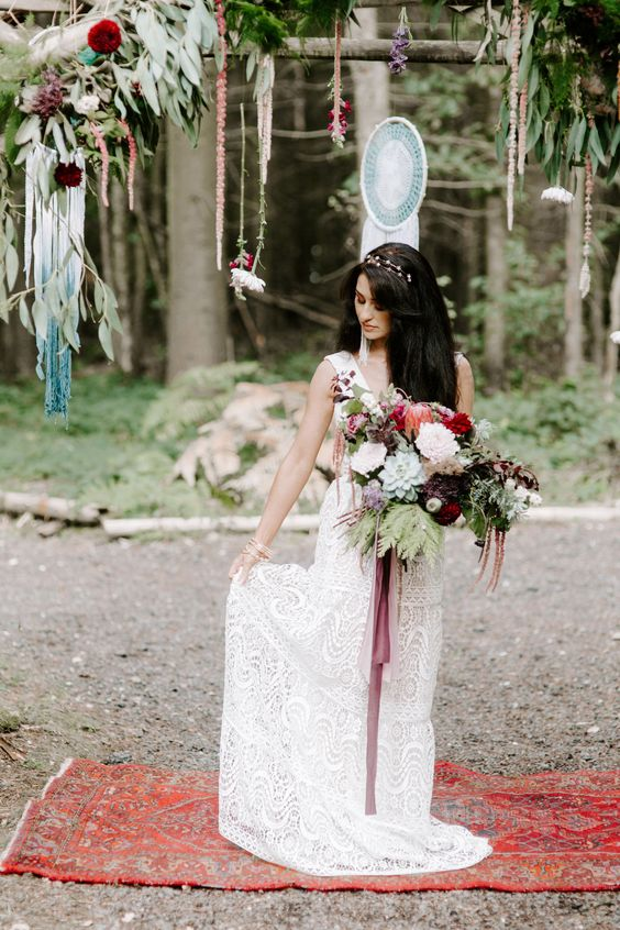 a bright boho woodland wedding arch with lots of greenery and bold blooms, macrame and long fringe plus a boho rug