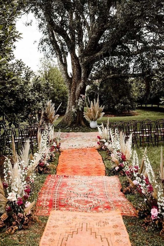 a bright boho woodland wedding ceremony space with boho rugs, pampas grass, bold and neutral blooms and lots of foliage and greenery