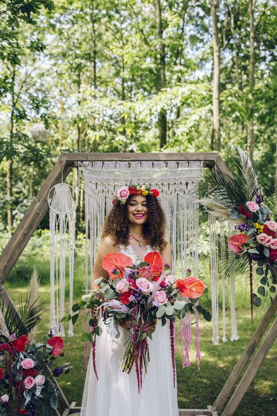 a bright summer boho wedding arch - a hexagon with macrame, fringe, bold blooms and foliage is a wow idea