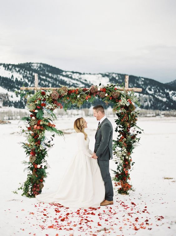 a bright winter woodland wedding arch made of branches, with evergreens, white and red blooms and leaves