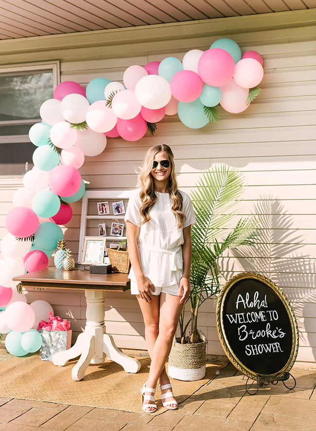 a casual summer bridal shower look with a white top and shorts, white heels with straps and sunglasses