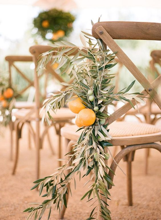 a chair decorated with olive branches with olives and lemons is a cool idea for a Mediterranean wedding