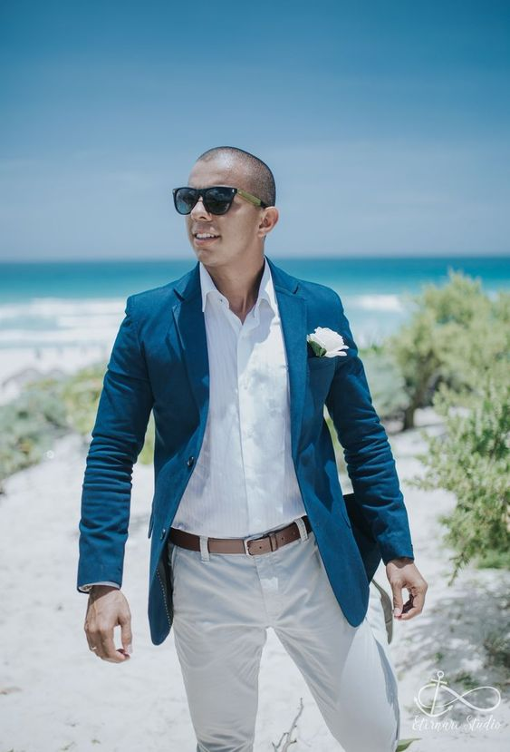a chic beach groom's look with a white shirt, white pants, a bold blue blazer and a white bloom boutonniere