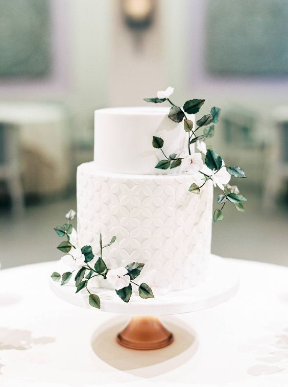 a chic white wedding cake with a plain and geometric tier, with white blooms and green leaves