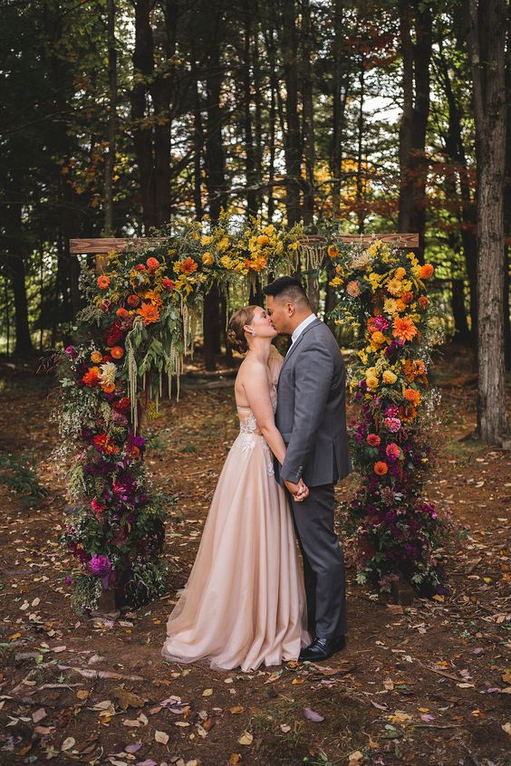 a colorful floral wedding arch with greenery will stand out a lot in any woodland or forest and will fit a summer or fall wedding
