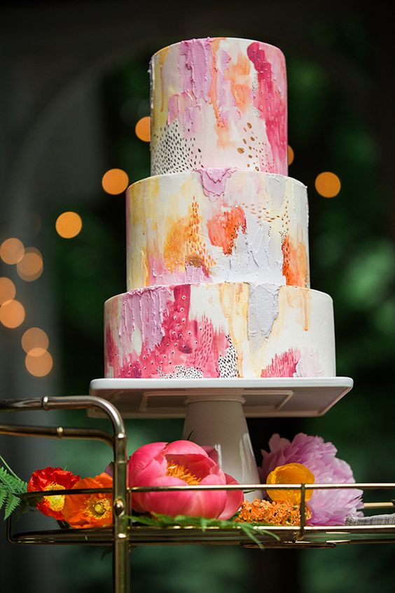 a colorful textural wedding cake in pink, coral, yellow and orange plus gold splashes is very chic
