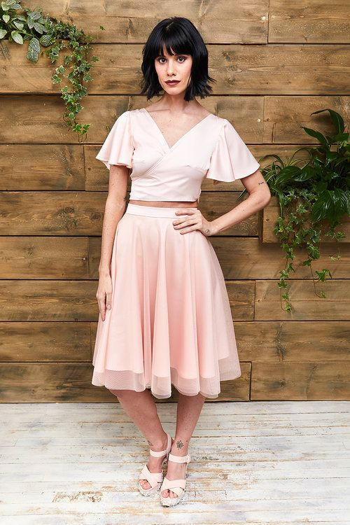 a cool ensemble of a pink silk crop top with bell sleeves and a V neckline plus a knee pleated skirt and platform shoes