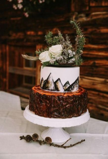 a cool mountain wedding cake with a bark tier and a painted mountain one plus wildflowers and evergreens on top
