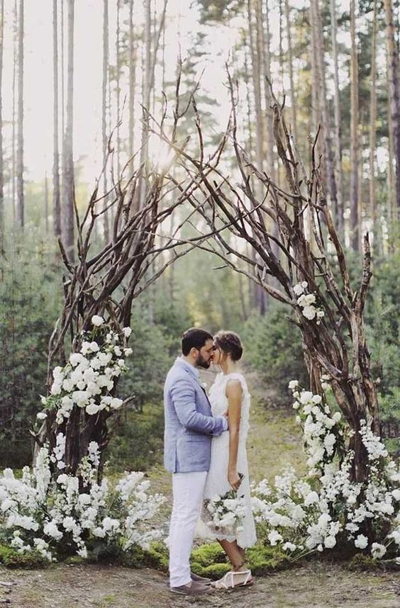 a cool spring woodland wedding altar of branches, white blooms and greenery and moss on the ground is a cool idea