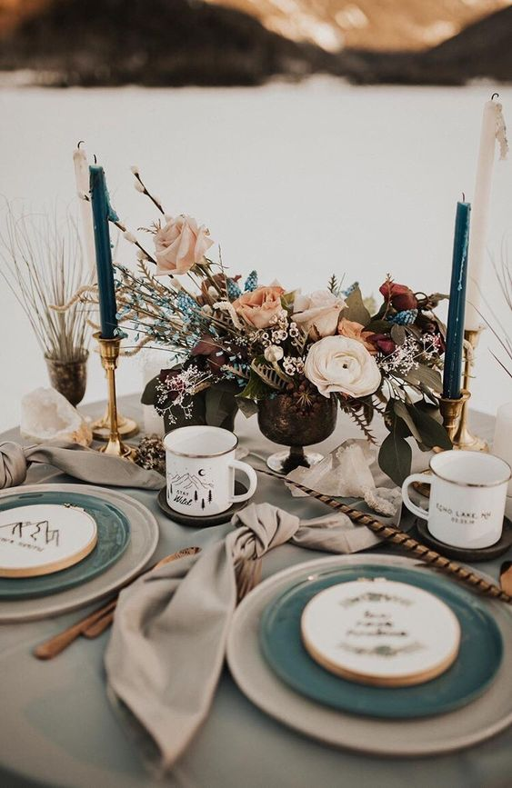 a cool winter mountain wedding table with a lush floral centerpiece, teal candles, plates and metal mugs and a embroidery hoops with mountains
