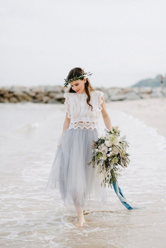 a creative beach bridal look with a white lace crop top with no sleeves and a powder blue midi tulle skirt