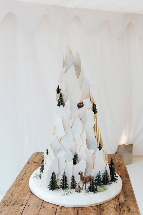 a creative shard wedding cake showing off a mountain with trees, deer and other animals