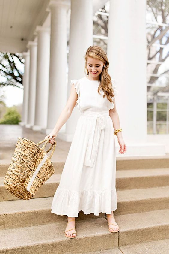 a cute plain white midi dress with ruffles and a sash, nude sandals and a straw bag for a casual summer bridal shower look