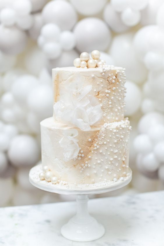 a delicate and refined white pearl wedding cake with sugar blooms and large pearls on top