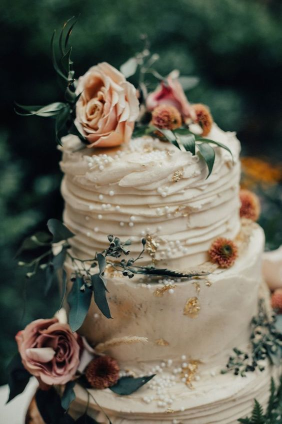 a dreamy neutral textural wedding cake with gold leaf, blush blooms and greenery plus edible pearls
