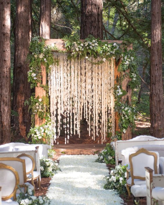 a fairytale woodland wedding arch of wood, with greenery and white blooms plus white bloom garlands hanging down