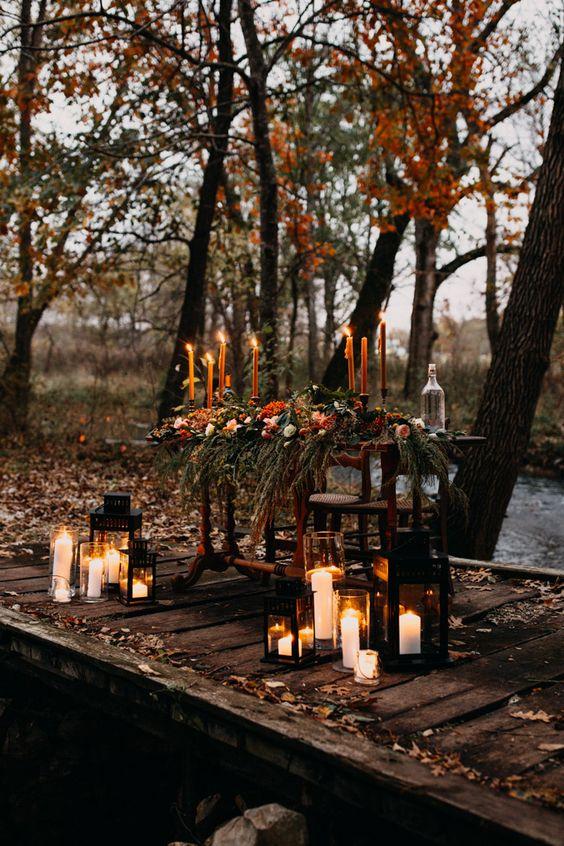 a fall boho woodland reception table with greenery, bright blooms and candles, candle lanterns around it looks wow