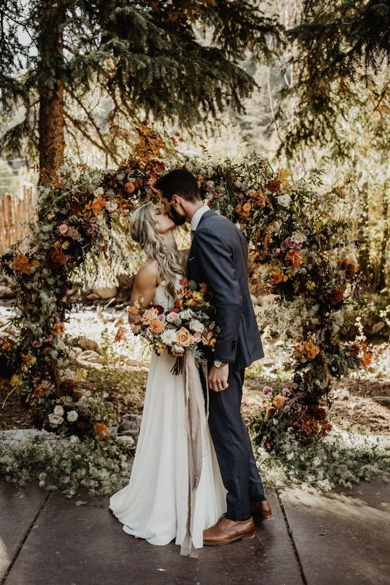 a fall woodland round wedding arch of dried blooms and leaves, bright flowers and lots of greenery is very cool