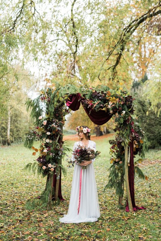 a fall woodland wedding arch of greenery, fall leaves, bold blooms and burgundy velvet fabric is a lovely and chic idea
