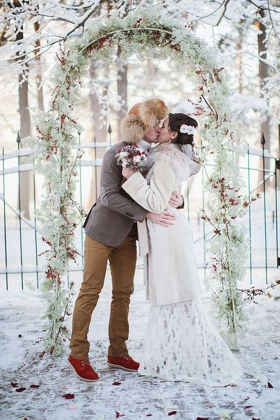 a frozen winter woodland wedding arch of baby's breath, red berries and cotton is a lovely idea for a snowy wedding