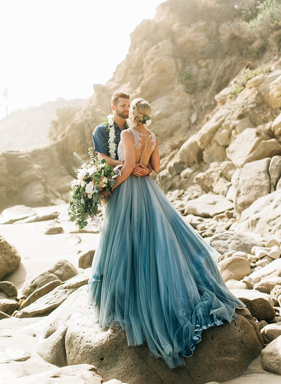 a gorgeous sleeveless wedding dress with a white lace bodice and a blue layered skirt with a train for a beach bride