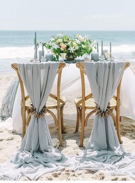 a light blue beach wedding tablescape with light blue candles, glasses, plates and linens, neutral blooms and driftwood