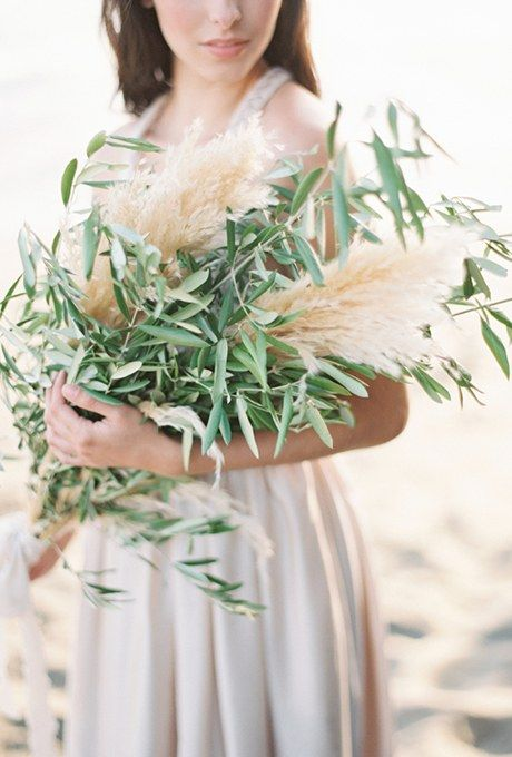 a lush wedding bouquet of pampas grass and olive branches is a creative and bold idea for a natural bride