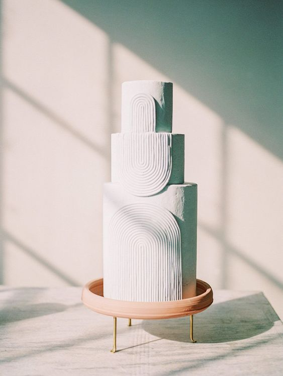 a modern white wedding cake with textural detailing is a chic and refined idea for a contemporary wedding