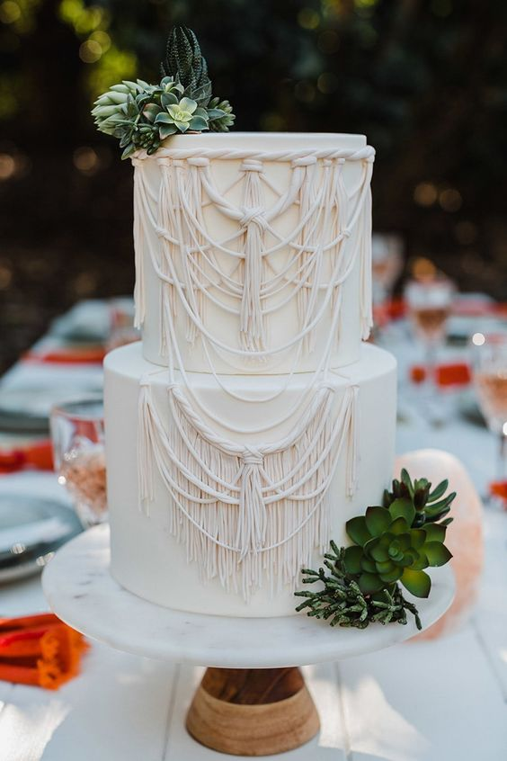 a neutral boho wedding cake with macrame patterns and succulents and greenery is very bold and cool