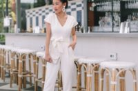 a plain white jumpsuit with a V-neckline, a sash and a bow, statement earrings, nude heels and a white clutch