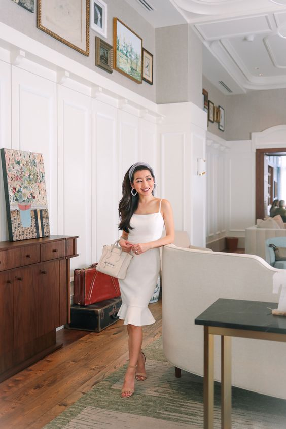 a plain white spaghetti strap knee dress with a ruffle skirt, nude heels and a cute bag for a modern and romantic bride-to-be