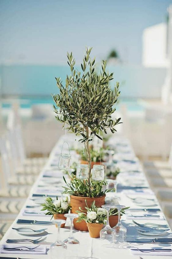 a potted olive mini tree with candles in jars hanging on it is a cool and eco-friendly centerpiece for any wedding
