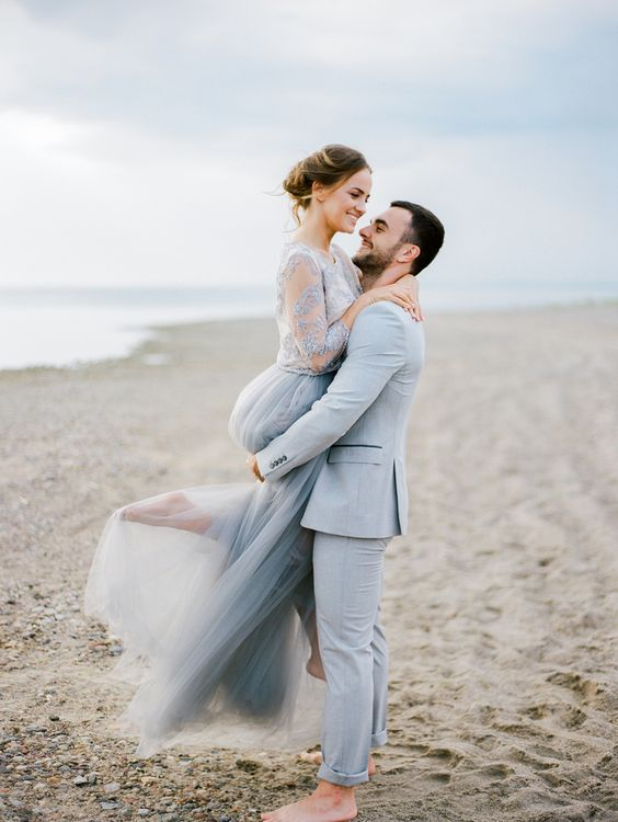 a powder blue suit for the groom and a blue lace embellished top with short sleeves and a blue tulel skirt for the bride