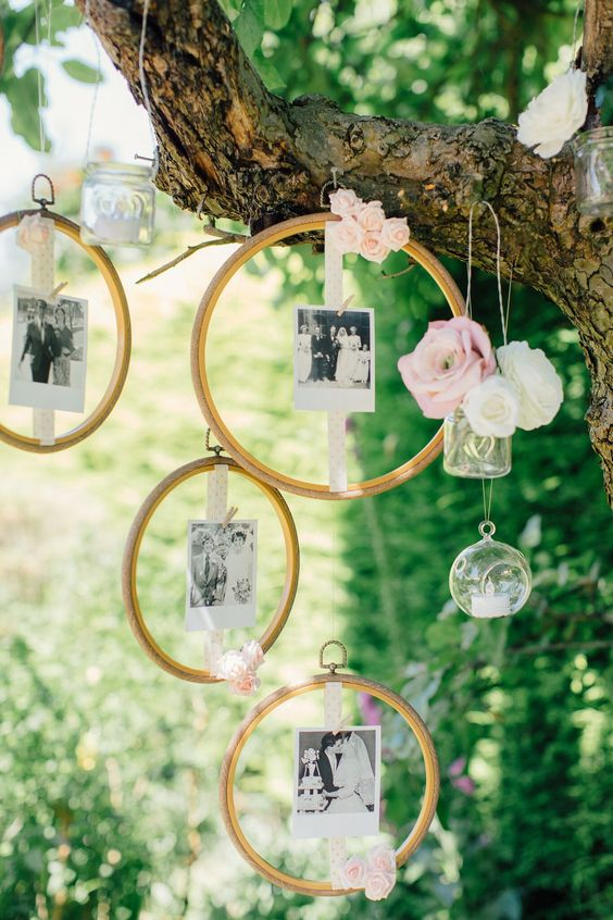 a real tree with fresh blooms in vases and candles plus family photos attached to embroidery hoops