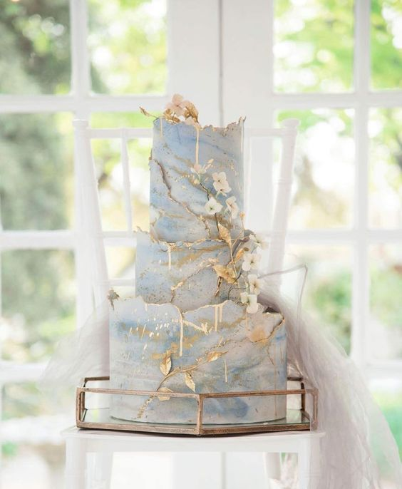 a refined blue and white marble wedding cake with a gold edge and sugar blooms and gold leaves for a formal wedding
