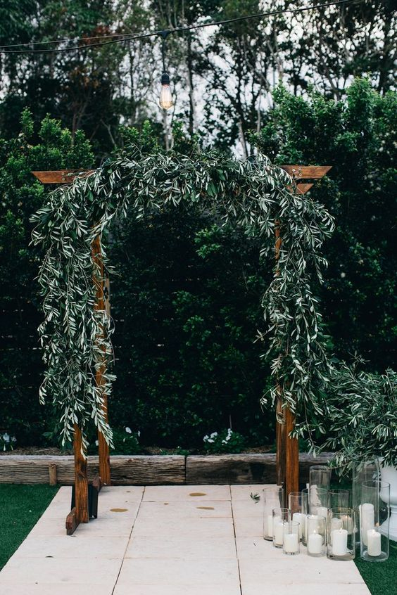 a rich stained wedding arch decorated with olive greenery and candles in glasses for a simple and chic look